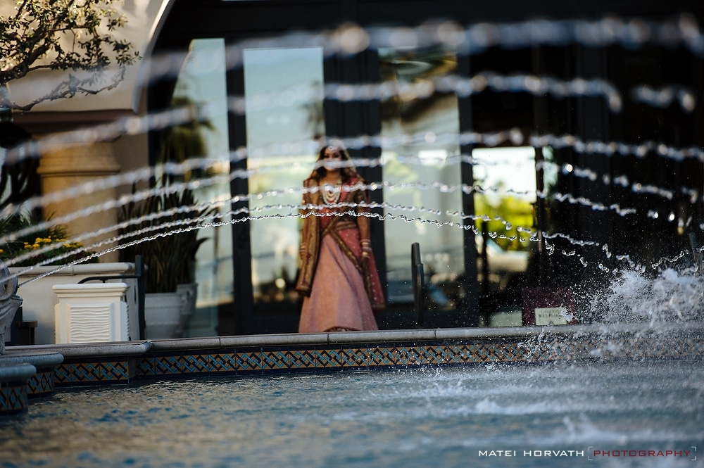 The bride is emerging behind the water fountain at Hyatt Regency Huntington Beach