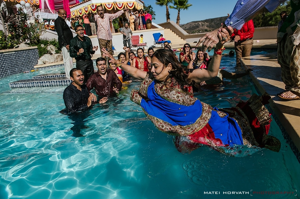 The bride's and groom's families jump in the pool.