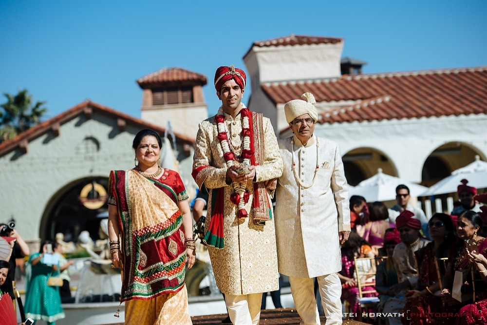 The groom and his parents walking down the isle